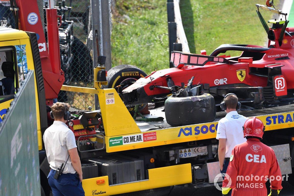 Los oficiales de pisa con el coche dañado de Carlos Sainz Jr., Ferrari SF21