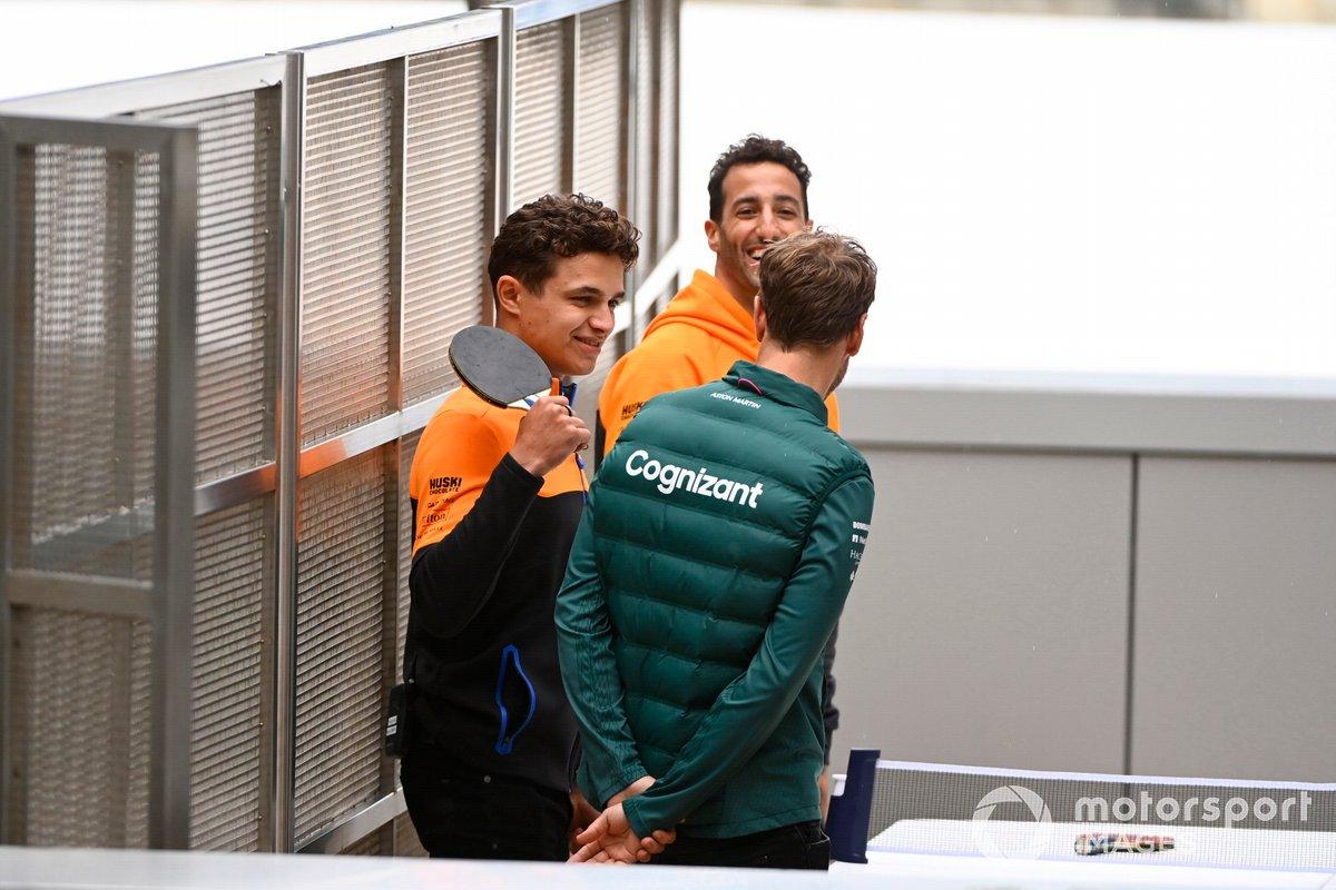 Daniel Ricciardo, McLaren, y Sebastian Vettel, Aston Martin, jugando al ping-pong con Lando Norris, McLaren