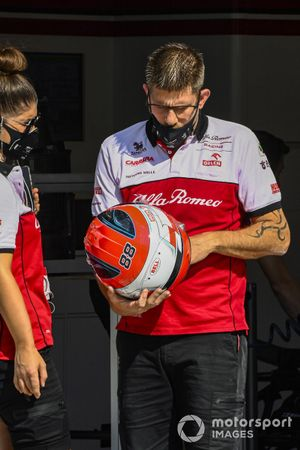 Alfa Romeo monteur met de helm van Robert Kubica