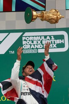 Lewis Hamilton, Mercedes AMG F1, 1st position, tosses his trophy in to their in celebration on the podium