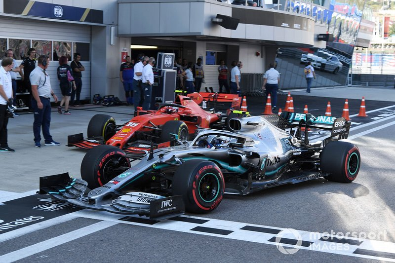 Charles Leclerc, Ferrari SF90, and Valtteri Bottas, Mercedes AMG W10, in the pit lane