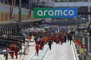 Mechanics in the pit lane at the start