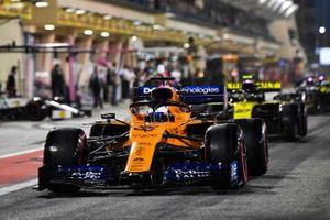 Carlos Sainz Jr., McLaren MCL34, leads Nico Hulkenberg, Renault R.S. 19, in the pit lane