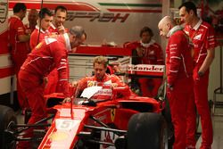 Sebastian Vettel, Ferrari, lowers himself into the cockpit of his car, which is fitted with a new pr