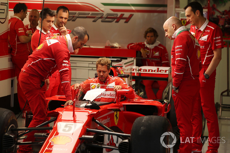 Sebastian Vettel, Ferrari, lowers himself into the cockpit of his car, which is fitted with a new protective windscreen shield