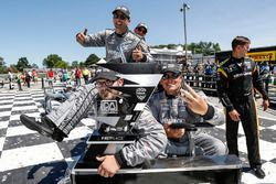 Josef Newgarden, Team Penske Chevrolet, team members go back to the transporter with the trophy, podium