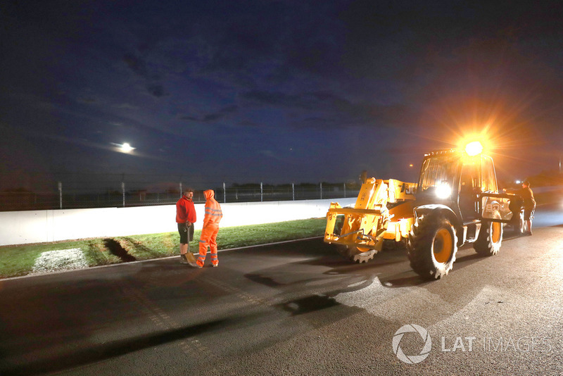 Crews work to improve drainage on the circuit before Sunday's race