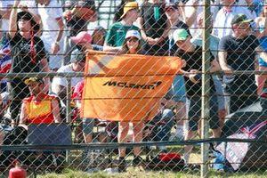 A McLaren fan holds up a flag