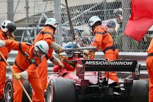 Marshals remove the car of Charles Leclerc, Ferrari SF21, from the circuit