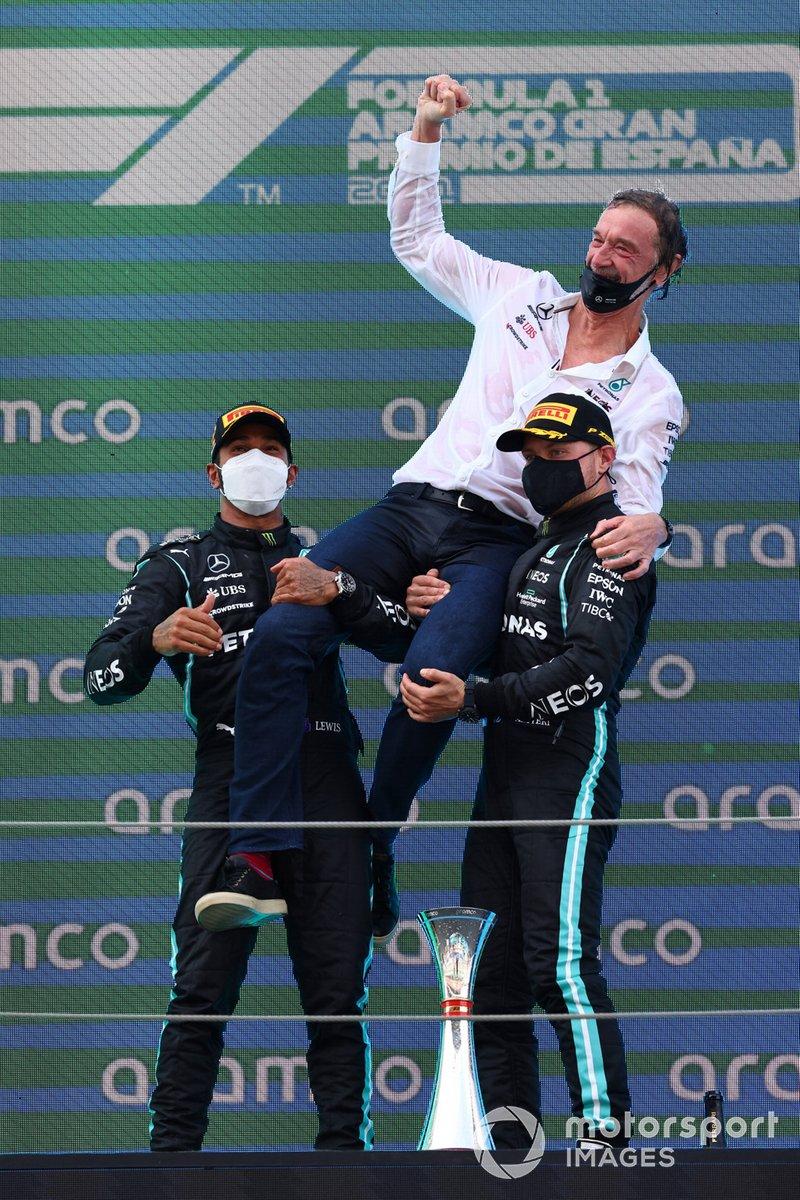 Lewis Hamilton, Mercedes, primera posición, el encargado de Mercedes de recoger el trofeo y Valtteri Bottas, Mercedes, tercera posición, en el podio