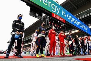 The drivers stand in line for the national anthems on the grid prior to the start