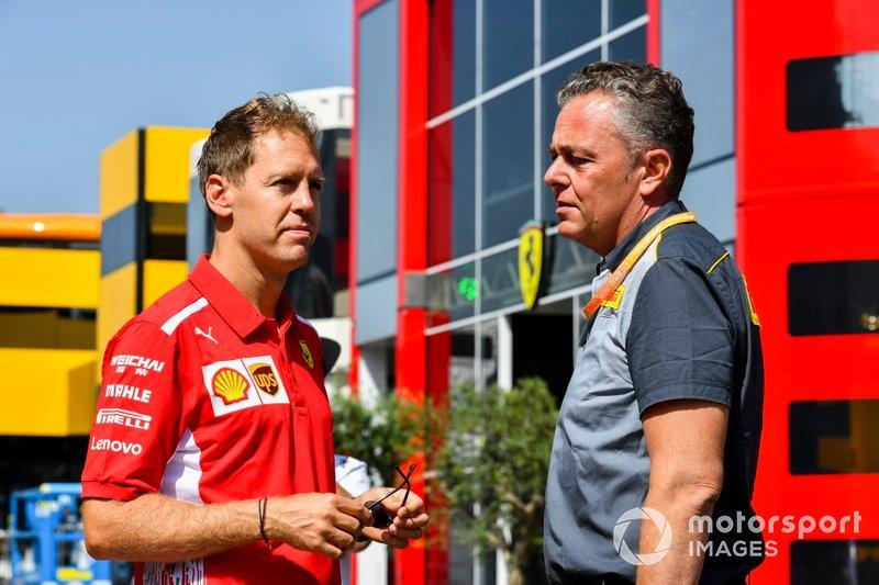 Sebastian Vettel, Ferrari et Mario Isola, directeur de la compétition de Pirelli Motorsport, parlent dans le paddock