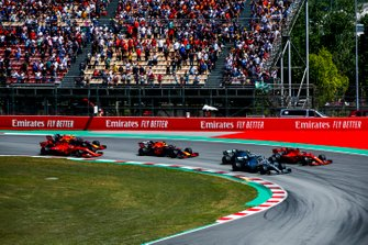 Lewis Hamilton, Mercedes AMG F1 W10, Valtteri Bottas, Mercedes AMG W10, and Sebastian Vettel, Ferrari SF90, race side by side ahead of Max Verstappen, Red Bull Racing RB15, Charles Leclerc, Ferrari SF90, and Pierre Gasly, Red Bull Racing RB15, in the first corner at the start