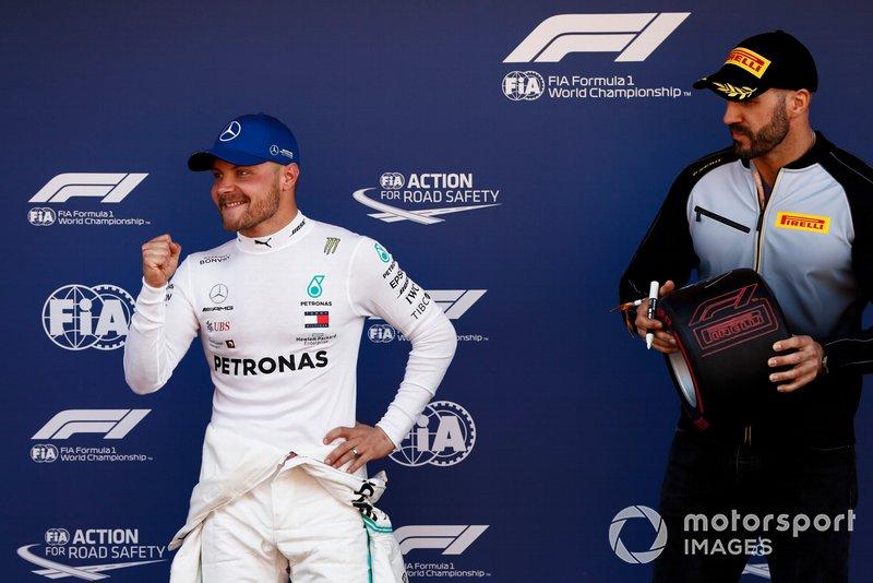 Pole man Valtteri Bottas, Mercedes AMG F1, celebrates as WWE wrestler Cesaro waits to award him his Pirelli Pole Position award