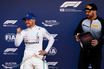 Pole man Valtteri Bottas, Mercedes AMG F1, celebrates as WWE wrestler Cesaro waits to award him his Pirelli Pole Position award