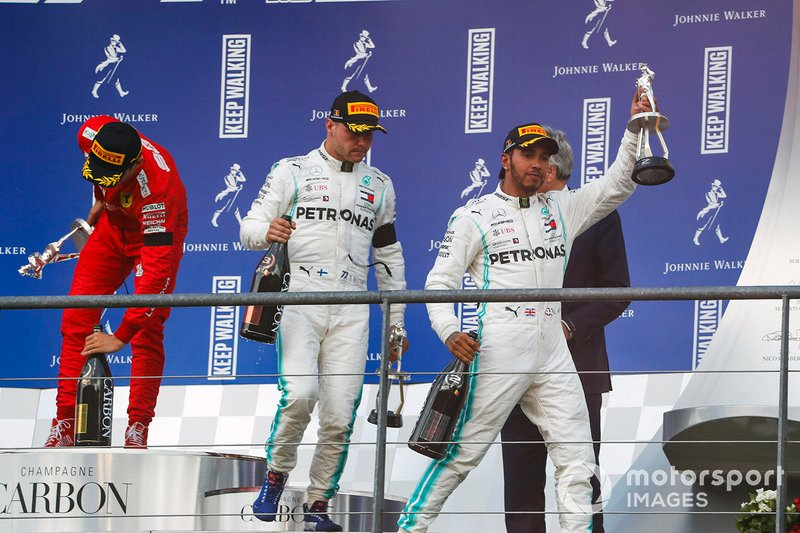 Lewis Hamilton, Mercedes AMG F1, secondo classificato, Valtteri Bottas, Mercedes AMG F1, terzo classificato, e Charles Leclerc, Ferrari, primo classificato, lascia il podio