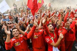 The Ferrari team gather to celebrate victory at the podium