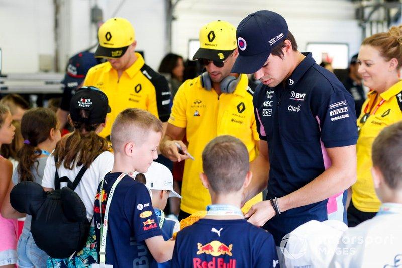 Lance Stroll, Racing Point, Daniel Ricciardo, Renault F1 Team e Nico Hulkenberg, Renault F1 Team firma autografi per i Grid Kids