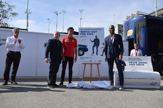 Jean Todt, Presidente de la FIA, Charles Leclerc, Ferrari y el futbolista Didier Drogba presentan un cartel en una campaña de conducción más segura