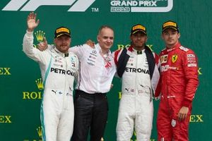 Valtteri Bottas, Mercedes AMG F1, 2nd position, the Mercedes Constructors trophy delegate, Lewis Hamilton, Mercedes AMG F1, 1st position, and Charles Leclerc, Ferrari, 3rd position, on the podium