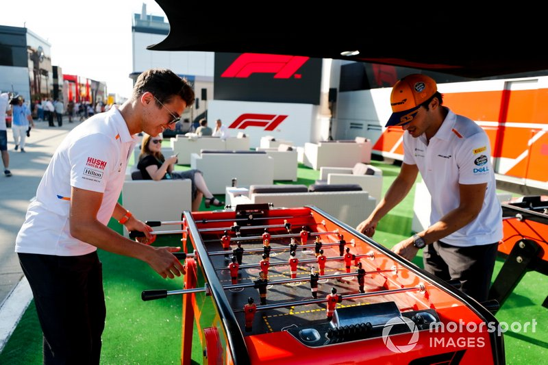 Lando Norris, McLaren and Carlos Sainz Jr., McLaren play table football in the paddock