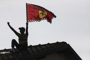Ferrari fans find their way onto a rooftop with a flag