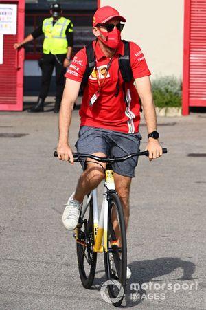 Sebastian Vettel, Ferrari, cycles into the paddock