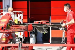 Ferrari team members carry the nose of a Ferrari SF21