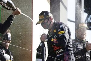 Lewis Hamilton, Mercedes, 2nd position, sprays Champagne at Max Verstappen, Red Bull Racing, 1st position, on the podium