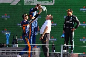 Daniel Ricciardo, McLaren, 1st position, Lando Norris, McLaren, 2nd position, and Zak Brown, CEO, McLaren Racing, celebrate on the podium with shoeys
