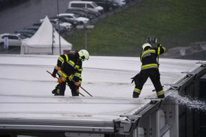 Water is cleared by firemen from a roof with brooms