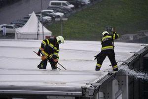 Пожарные используют швабры для избавления от воды под дождем