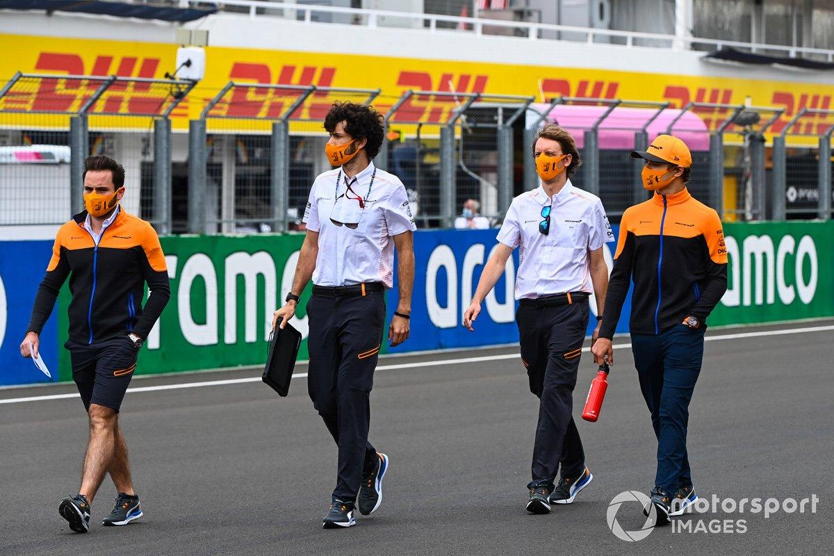 Lando Norris, McLaren, walks the track with team members