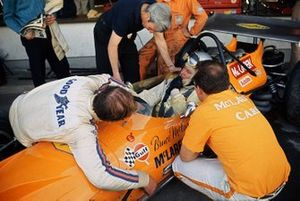 Bruce McLaren, McLaren M14A-Ford, in conversation with Teddy Mayer and lying over the car, team mate Denny Hulme