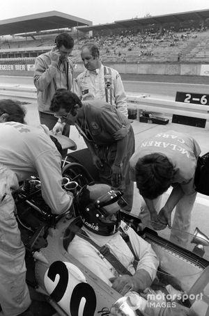 Denny Hulme stands behind Andrea de Adamich, McLaren M14D Alfa Romeo in the pit lane