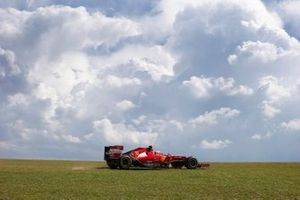 Kimi Raikkonen, Ferrari F14T, runs across the grass