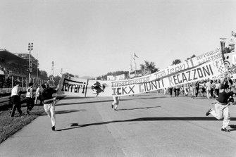 Tifosis sostienen una bandera de Ferrari en la recta principal