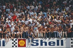 Spectators watch from improvised seating on a Shell advertising hoarding