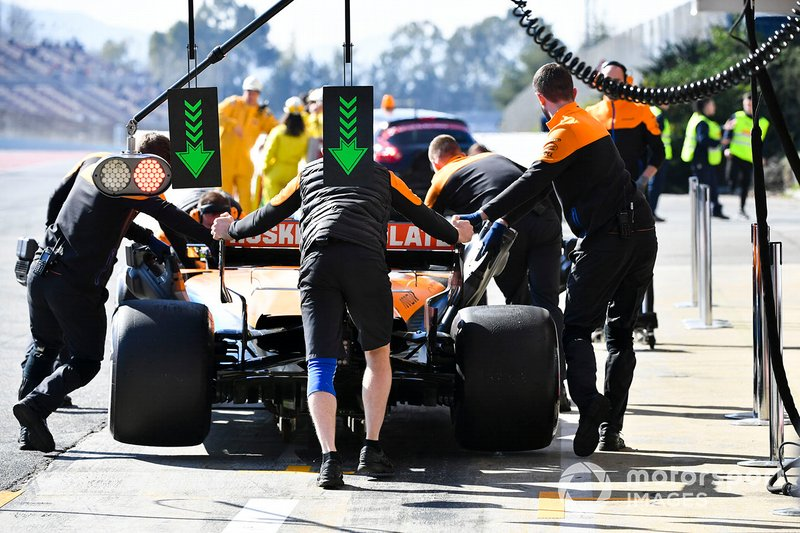 Car of Lando Norris, McLaren MCL35 being oushed in the pit lane by mechanics