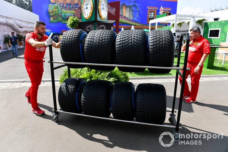 Ferrari mechanic with Pirelli wet tyres in the paddock