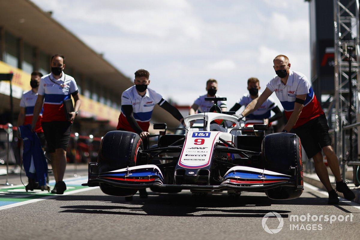 Los mecánicos empujan el coche de Nikita Mazepin, Haas VF-21, por el pitlane