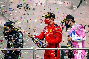 Sebastian Vettel, Ferrari, 3rd position, and Sergio Perez, Racing Point, 2nd position, spray Lewis Hamilton, Mercedes-AMG F1, 1st position, with Champagne on the podium