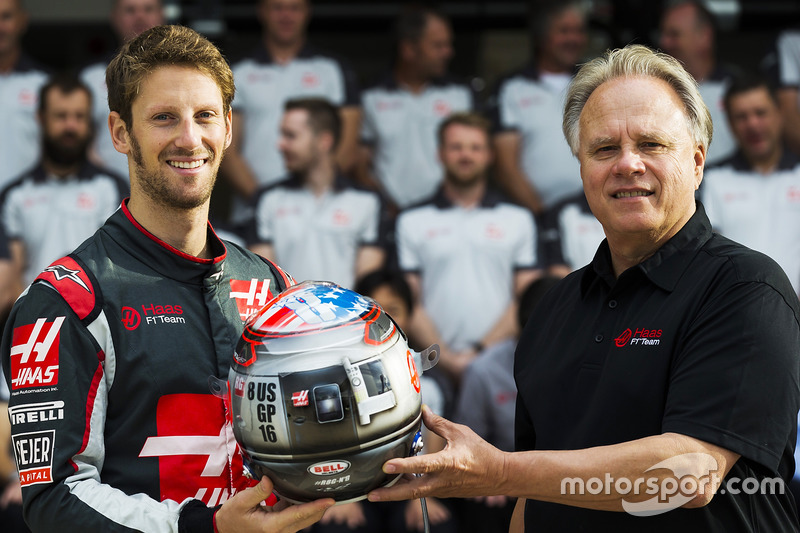 Romain Grosjean presents team owner Gene Haas with his commemorative helmet for the United States Grand Prix