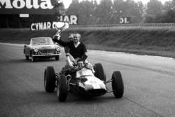 Победитель Джим Кларк провозит по трассе на своем Lotus 25 владельца команды Колина Чепмена