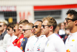 The drivers line up for the national anthem on the grid