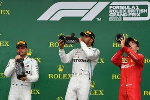 Valtteri Bottas, Mercedes AMG F1, 2nd position, Lewis Hamilton, Mercedes AMG F1, 1st position, and Charles Leclerc, Ferrari, 3rd position, drink from their Champagne bottles on the podium