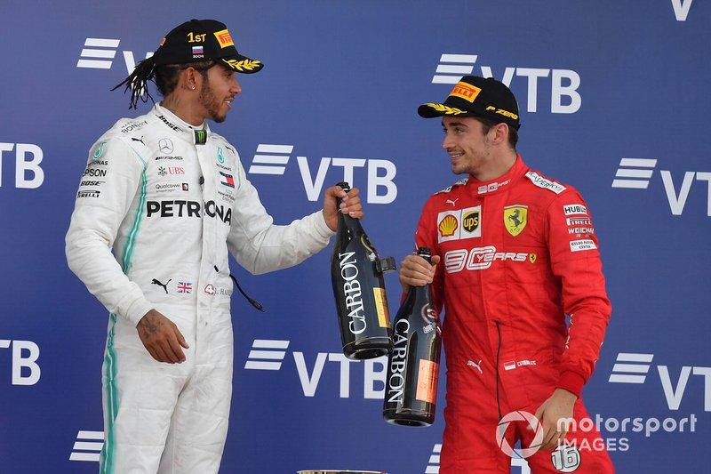 Lewis Hamilton, Mercedes AMG F1, primo classificato, e Charles Leclerc, Ferrari, terzo classificato, festeggiano con lo Champagne sul podio