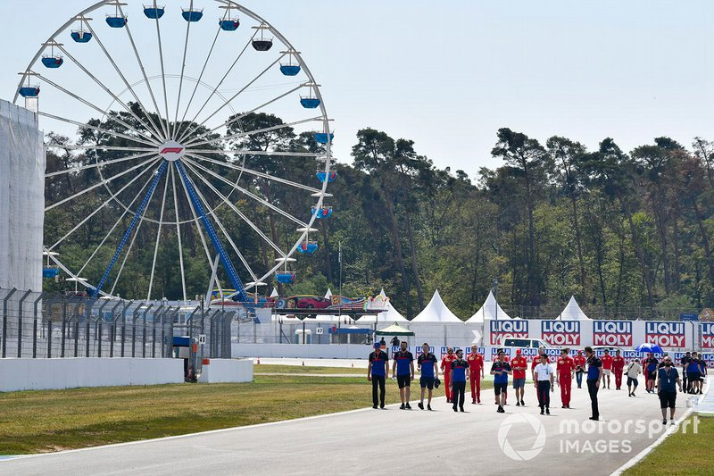 Daniil Kvyat, Toro Rosso y Naoki Yamamoto caminan por la pista con mecánicos