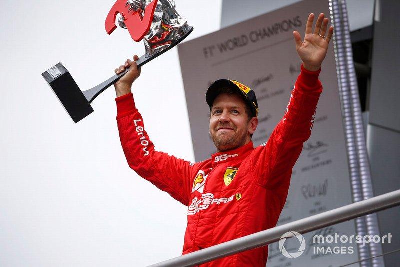 Sebastian Vettel, Ferrari, 2° classificato, sul podio, con il suo trofeo