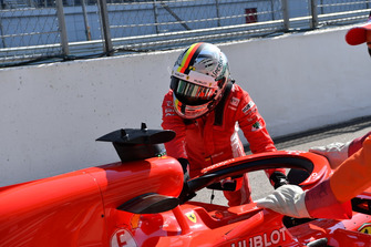 Sebastian Vettel, Ferrari empujan su auto hacia atrás en el pit lane